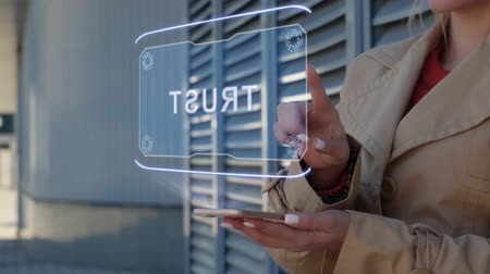 hűség : Unrecognizable businesswoman interacts HUD hologram with text Trust. Woman in the coat uses the technology of the future mobile screen on the background of the city