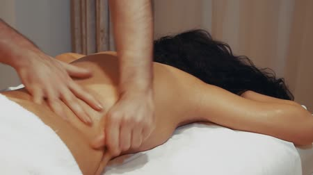 брюнет : Woman having massage in a spa salon. Male hands massage a female back lying on a massage table in slow motion Стоковые видеозаписи