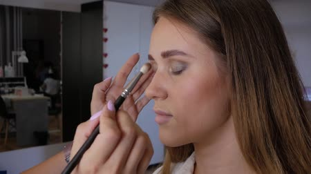 obrys : Client woman in beauty salon doing makeup close-up slowmotion. Hand of professional makeup artist applies a brush to the upper eyelid of left eye beautiful girl with a brush