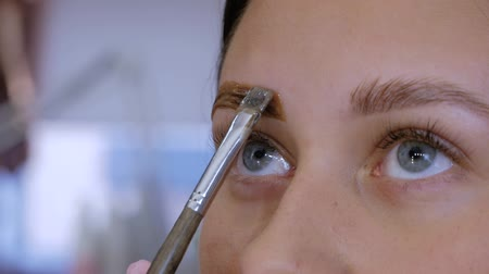 longer : Close up of female beautician hand applies paint with a brush on the eyebrows of a beautiful patient. Part of the eyebrow lamination procedure