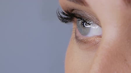 globo ocular : Eye of a young woman blinks in slow motion on a blue background. Beautiful female blue eye close-up