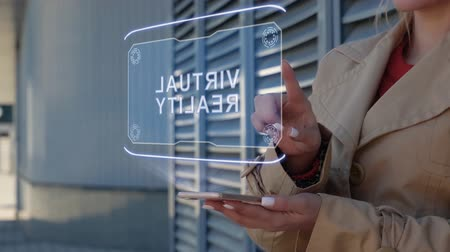 Unrecognizable businesswoman interacts HUD hologram with text Virtual Reality. Woman in the coat uses the technology of the future mobile screen on the background of the city