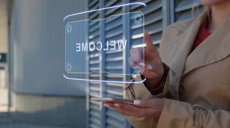 Unrecognizable businesswoman interacts HUD hologram with text Welcome. Woman in the coat uses the technology of the future mobile screen on the background of the city