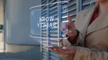 щит : Unrecognizable businesswoman interacts HUD hologram with text Work safety. Woman in the coat uses the technology of the future mobile screen on the background of the city Стоковые видеозаписи