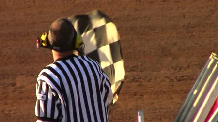 motor vehicle : Man Waving Checker Flag at Finish Line at Race Track Stock Footage