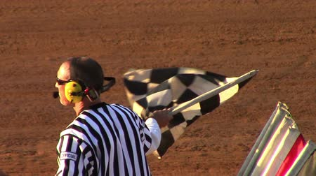 wyscigi : Man Waving Checker Flag at Finish Line at Race Track Wideo