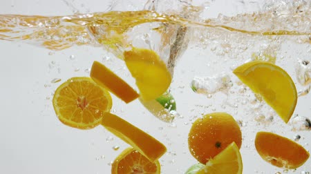 фрукты : Pieces of oranges and limes falling into water in slow motion Стоковые видеозаписи