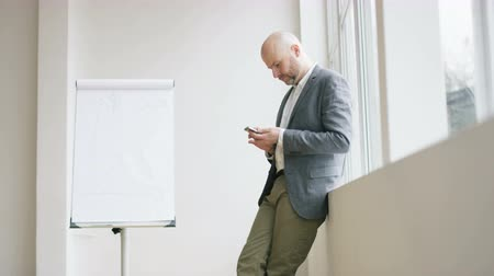 Bald Businessman Surfing on the Internet Via his Mobile