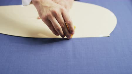 Hands of a Man Drawing an Oval Shape on a Blue Material