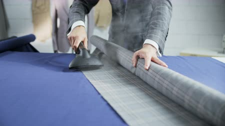 Man in a Suit Ironing a Grey Checked Piece of Material