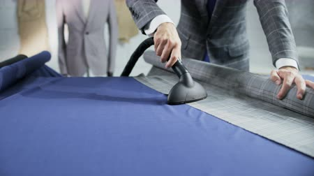 varrónő : Man in a Suit Ironing a Grey Checked Piece of Material