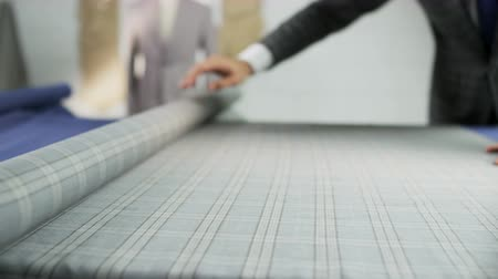 Man in a Suit Unrolling a Grey Checked Piece of Material Stock Footage