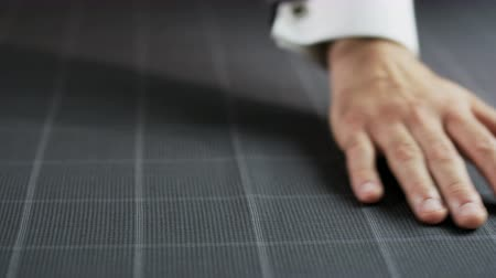 Man Moving his Hand on a Grey Checked Piece of Material Stock Footage