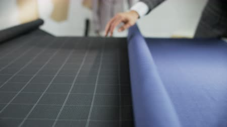 Man in a Suit Unrolling a Blue Piece of Material
