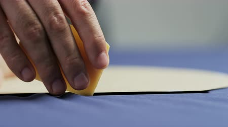 ruhakészítés : Hands of a Man Drawing a White Line on a Blue Material Stock mozgókép