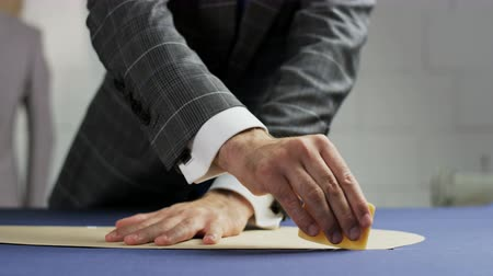 ruhakészítés : Man in a Suit Drawing a White Line on a Blue Material