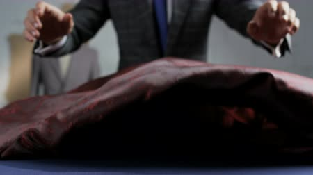 портной : Man in a Suit Putting a Dark Red Piece of Material on a Table