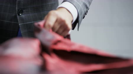 ruhakészítés : Man in a Suit Putting a Dark Red Piece of Material on a Table