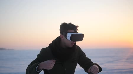 senzor : A man walks in the street in the winter in spectacular reality glasses and plays a game