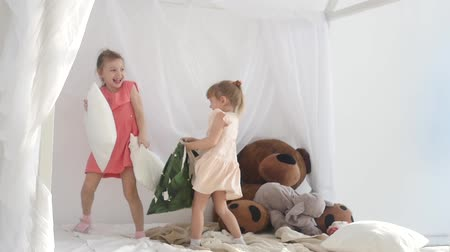 в помещении : Children fight with pillows. Happy sisters are fighting with pillows.