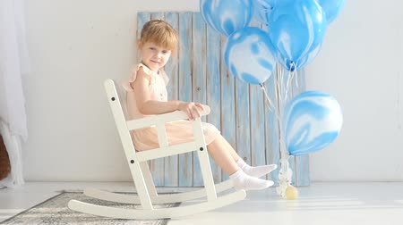 клетчатый : Beautiful little girl swinging in a rocking chair at the bottom of a birth
