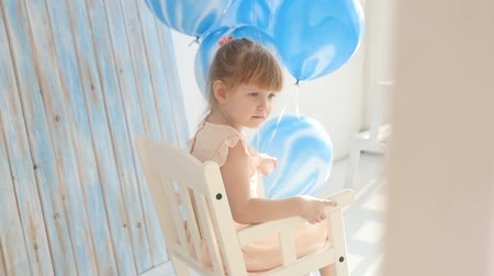 nurture : Beautiful little girl swinging in a rocking chair at the bottom of a birth