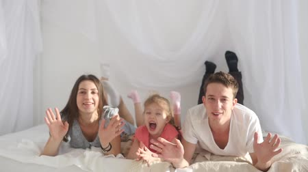 yatak kıyafeti : Happy young family lying on the bed waving their hands in the camera and laughing