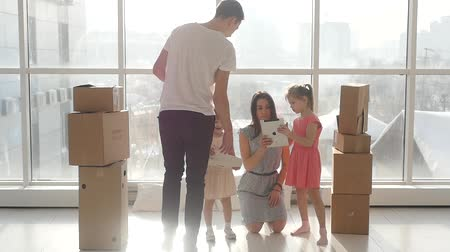 picture box : Happy young family in a new apartment, with children playing in the tablet. Happy Stock Footage