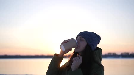buharlama : Woman Drinks Hot Tea or Coffee From Cup at Winter. Beautiful Girl Enjoying Winter Outdoors with a Mug of Warm Drink. Christmas Holidays