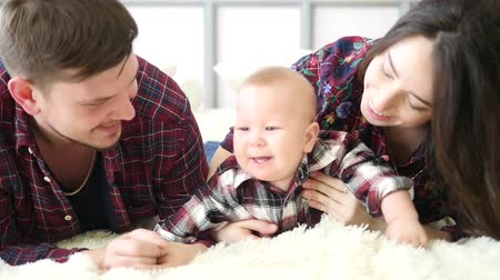 утешитель : Happy parents lying with their cute baby son on bedat home in bedroom