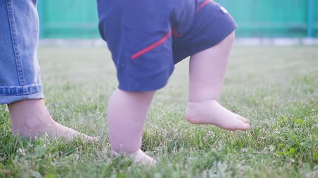 Little kid man legs, barefoot walking on a ground, meadow. Baby feet on the grass. Slow motion Stock mozgókép