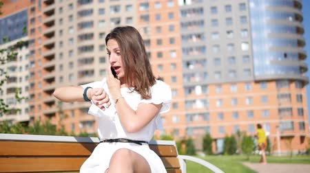 Beautiful girl in the city in a dress and with a smartphone. Late at the writing Stock mozgókép