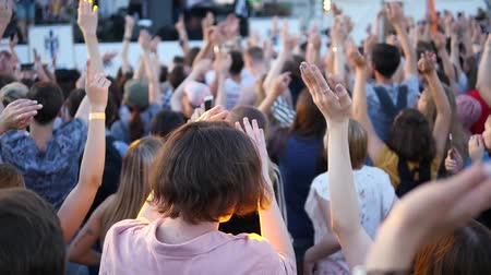 A large number of people at a concert raise their hands