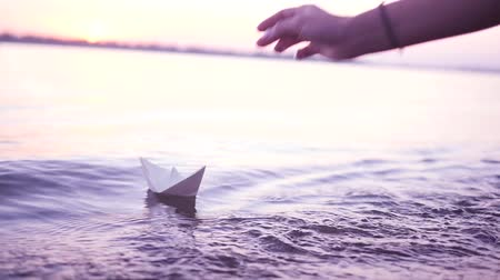 Man with a paper boat in water over beautiful sunset. Origami ship Sailing. Dreams, future, freedom or hope concept. Stock mozgókép