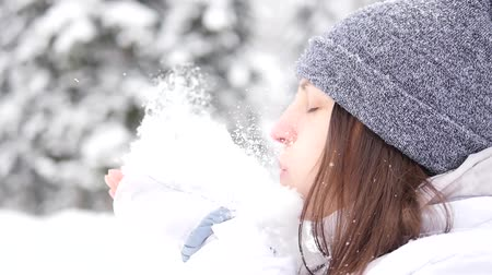 Blowing Snow. Beautiful girl blowing snow outdoors. Enjoying nature. Slow motion video footage 240 fps. Slowmo