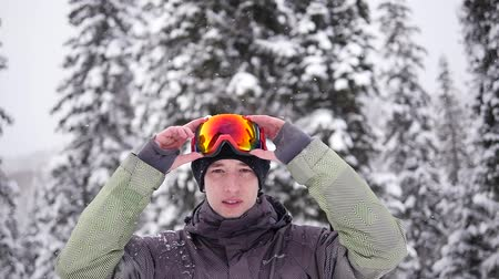 A young man at a ski resort puts on a mask before riding. It is snowing in the background