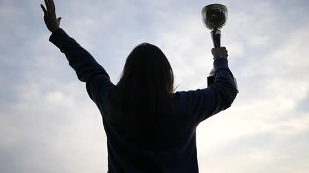Girl Run and Rise Her Hands With Golden Cup Over Head and Celebrate Her Victory. the Action in the Real Time.