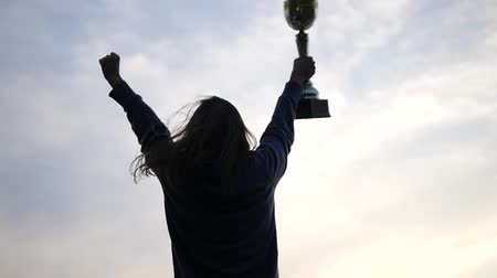 prêmio : Girl Run and Rise Her Hands With Golden Cup Over Head and Celebrate Her Victory. the Action in the Real Time.