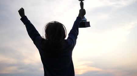 head over : Girl Run and Rise Her Hands With Golden Cup Over Head and Celebrate Her Victory. the Action in the Real Time.