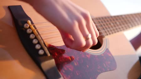 Close up of woman hands playing the guitar in the beautiful sunset slow motion
