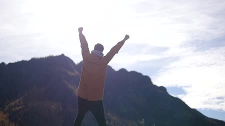 A man stands on the top of a mountain. A man raises his hands a winner after climbing the mountain. Joy of victory