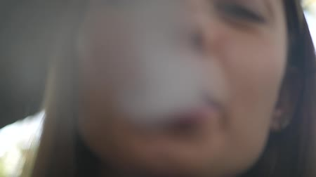 Woman smokes a hookah. Close up of the face in smoke