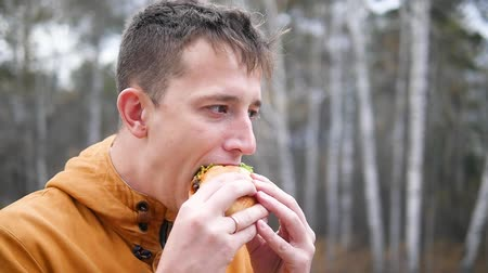 Man eats a hamburger Stock mozgókép