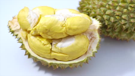 очищенные : Still life photography of Durian the king of tropical fruits on white background with path, shooting in studio. Popular dessert in Thailand served with sticky rice and fresh coconut milk on topping. Tropical fruits concept. Стоковые видеозаписи