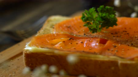 全粒 : Smoked salmon served with Whole grain bread toasted, dolly shot on table.