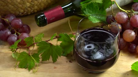 winogrona : Slow motion clip of drop red wine in crystal glass, organic fresh grapes and empty bottle on background, The best of drink in holiday and celebration ideas concept, free space for text. Wideo