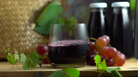 Slow motion of grape juice in glass bottle pouring into crystal glass, organic fresh grapes on background, The best of drink for healthy and holiday celebration ideas concept, free space for text.