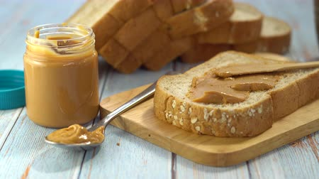 Peanut butter served with whole wheat bread. Healthy food, Nutrition fact and clean food good taste ideas concept. Bread with peanut butter on a wooden plate.