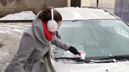 hangtompító : Cute young woman removing ice from car windshield
