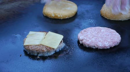 finomkodik : Cook uses a blow torch to melt cheese on a meat cutlet. Chef melts cheese on a burger using a blow torch.